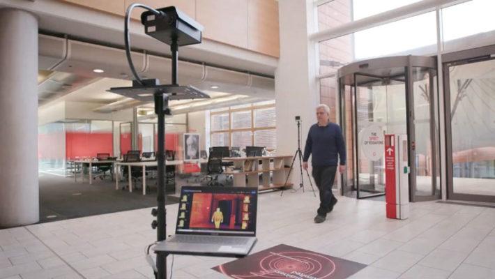 有一個人進入大樓並走過熱成像攝影機以進行體溫量測。